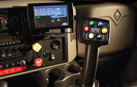 Uni-Grip™ 620 joystick shown mounted on an Armadillo Arm Unit with a SpreadSmart Rx™ color display used by snowplow trucks for snow and ice removal